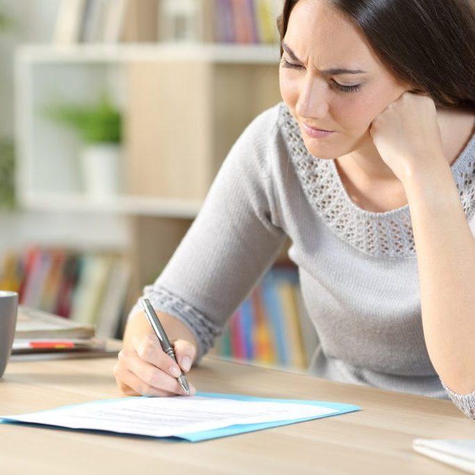 Confused woman checking and signing contract looking hesitant sitting on a desk at home
